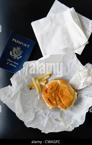 US passport with hamburger and fries - Stock Photo