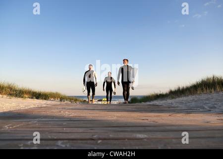 Three surfers walking on boardwalk - Stock Photo