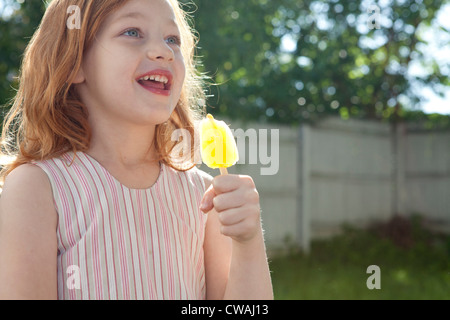 Girl holding ice lolly - Stock Photo