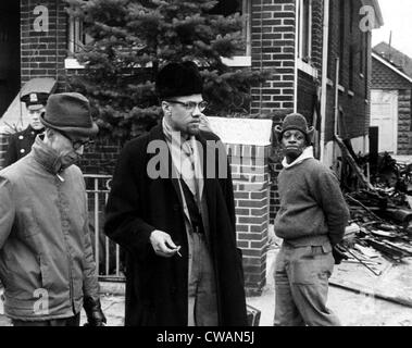 Malcolm X (center, 1925-1965), talks to a reporter after a fire bomb was thrown in his house. February 14, 1965. - Stock Photo