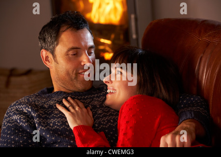 Middle Aged Couple Chatting On Sofa By Cosy Log Fire - Stock Photo
