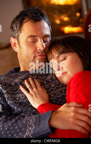 Middle Aged Couple Cuddling On Sofa By Cosy Log Fire - Stock Photo