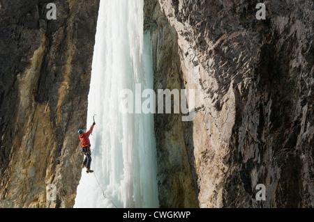 A man ice climbing a frozen waterfall, Silverton, Colorado. - Stock Photo