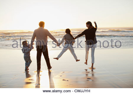 Family holding hands on beach at sunset - Stock Photo