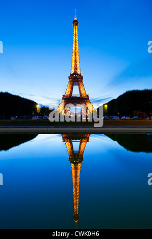 Paris Eiffel tower illuminated at night from the Champs de Mars gardens reflected in a pool Paris France EU Europe - Stock Photo