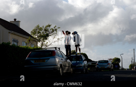 Male youths standing on car roof,auto, blue, body, boy, car, casual, child, clear, clothing, concept, copy-space, - Stock Photo