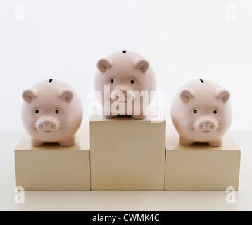 Three piggy banks in arranged on sports podium - Stockfoto