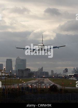 British Airways Embraer 190 aircraft landing at London City Airport, with the financial district visible in the - Stock Photo