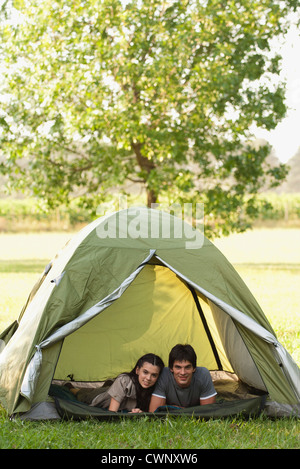 Young couple lying together in tent - Stock Photo