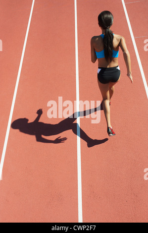 Female athlete running on track, rear view - Stock Photo