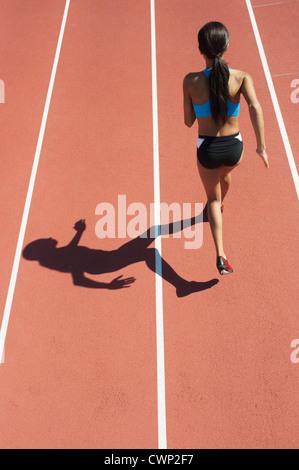 Female athlete running on track, rear view - Stockfoto