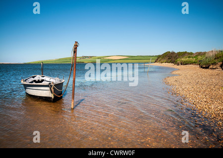 Boat moored on East Fleet next to Chesil Beach in Dorset, England, UK - Stock Photo