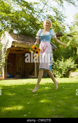 Woman carrying flowers in backyard - Stock Photo