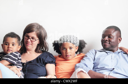 Family relaxing on sofa together - Stock Photo