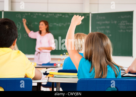 Girl putting her hand up in classroom - Stock Photo