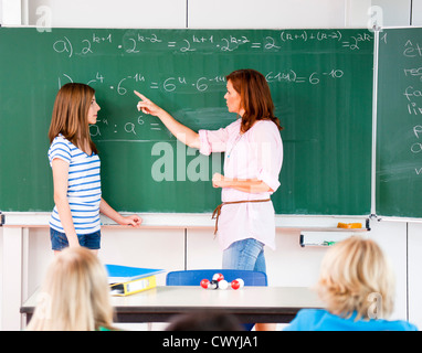 Schoolgirl with teacher at blackboard with formula - Stock Photo