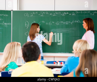 Schoolgirl writing formula at blackboard - Stock Photo
