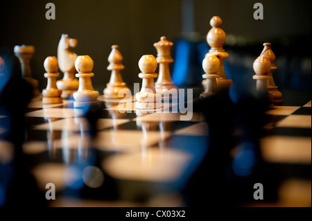 Carved wooden chess pieces on a chess board in warm light. - Stock Photo