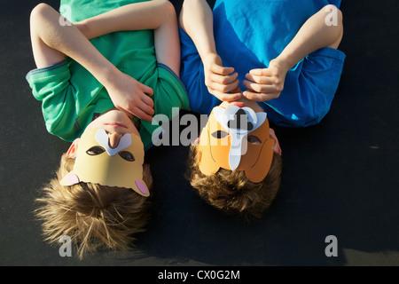 Two Boys Wearing Animal Masks lying on Back - Stock Photo