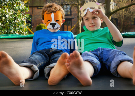 Two Boys Wearing Masks Lying on Trampoline - Stock Photo