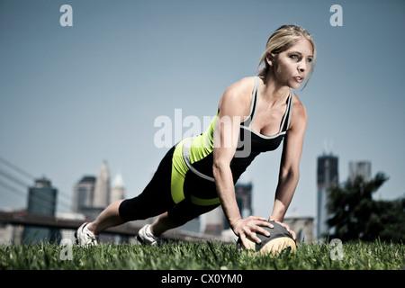 Woman doing push ups on ball - Stock Photo