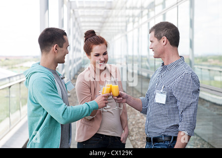 Colleagues toasting with orange juice - Stock Photo