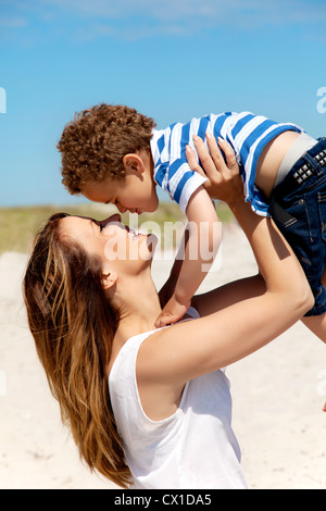 Beautiful young mom holding up her son - Stock Photo