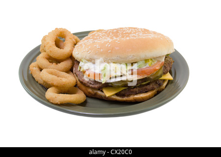double stack cheeseburger with tomato, lettuce, onions, mayo, pickles and onion rings on a green plate isolated - Stock Photo
