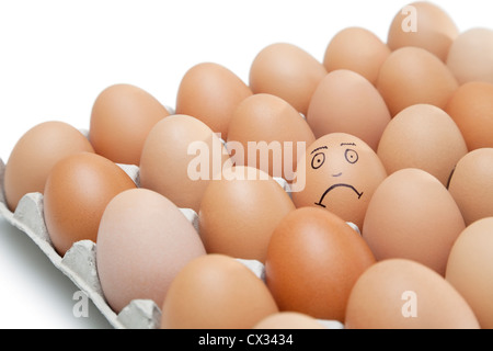 Sad face drawn on an egg surrounded by plain brown eggs in carton against white background - Stock Photo