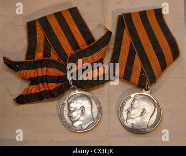 ITAR-TASS: ST PETERSBURG, RUSSIA. MARCH 29, 2012. Two Russian imperial silver medals featuring Tsar Nicholas II - Stock Photo