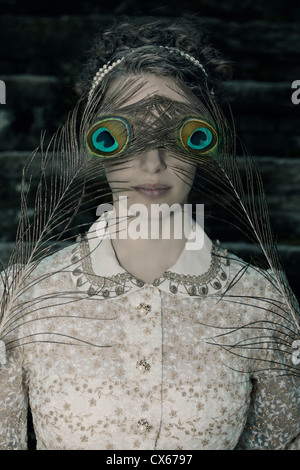 a woman with a victorian dress is holding two peacock feathers in front of her eyes - Stock Photo