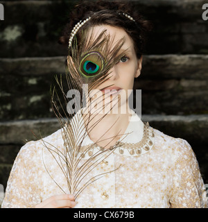 a woman with a victorian dress is holding a peacock feather in front of her eyes - Stock Photo