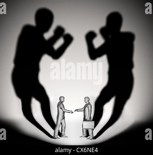 Two businessman casting a shadow shaped like two fighters - Stockfoto