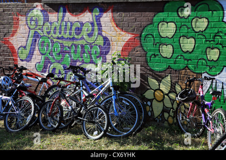 Bicycles in a school playground leaning against a mural painted on a wall. - Stock Photo
