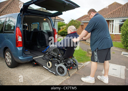 Male Carer son pushing a disabled elderly man in a wheelchair onto a built in ramp in a specially adapted car for - Stockfoto
