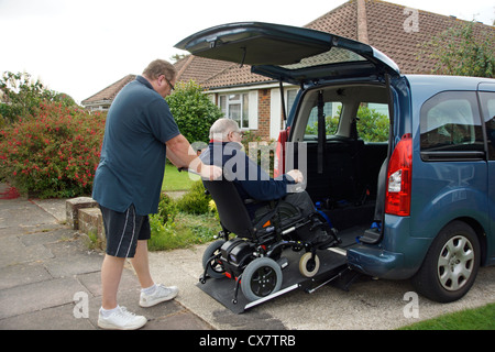 Male Carer son pushing a disabled elderly man in a wheelchair onto a built in ramp in a specially adapted car for - Stock Photo