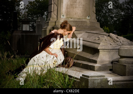 Young woman in victorian dress mourning on a tomb - Stock Photo