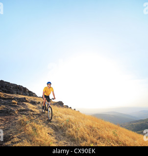 Male bicyclist riding a bicycle on a mountain - Stock Photo