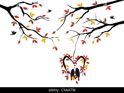 birds sitting on autumn tree in heart shaped nest - Stock Photo