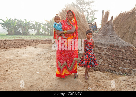 Mother in red sari and her two children in rural Bihari village at dawn, Sonepur, Bihar, India, Asia - Stock Photo