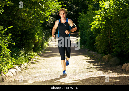 Sweaty man jogging while listening to music - Stockfoto