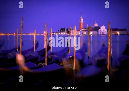 Gondolas at dusk with San Giorgio Maggiore island in the background, Venice, Italy, Europe. - Stock Photo