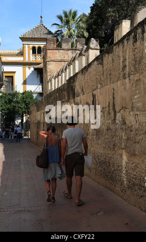 Young couple walking in the Juderia old jewish  part of tourist Seville along the wall of the Alcazar - Stockfoto