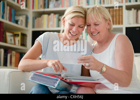 Family happiness and memories, happy mom and daughter looking at pictures in photo album - Stock Photo