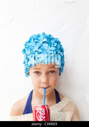 Girl in swimming cap drinking soda - Stock Photo