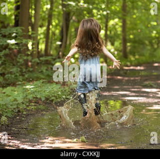 Little girl jumping in puddle - Stock Photo