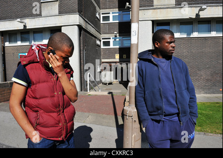 Two Young Unemployed Youth Leeds UK, one speaking on the phone. - Stock Photo
