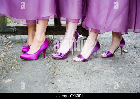 Bridesmaid's feet and ankles with purple high heeled shoes, showing hems of dresses. - Stock Photo