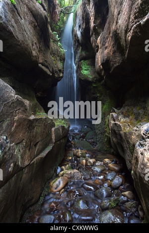 Isle of Eigg Waterfall in a limestone cavern close to the Singing Sands. - Stockfoto