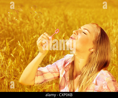 Image of cute blond girl blowing soap bubbles on wheat field, happy teenager having fun on golden crop meadow, closeup - Stock Photo
